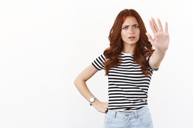 Serious-looking bossy redhead caucasian girl in striped t-shirt pull hand in stop motion, forbid step further, give prohibition, prevent friend from drinking alcohol, white wall