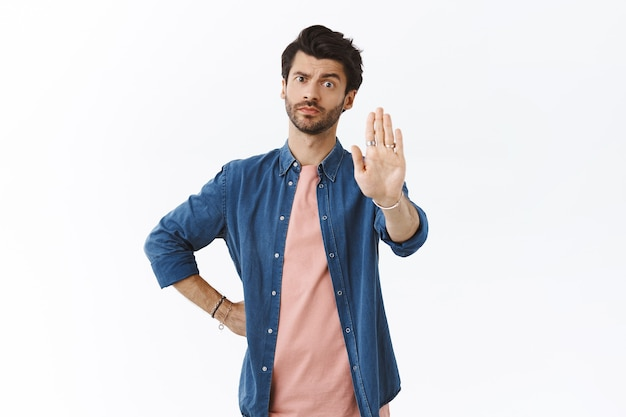 Серьезный озабоченный и напористый красивый мужчина, поднимает руку в знак запрета, предупреждает, недовольно ухмыляется и смотрит в камеру скептически, осуждающе, запрещает что-то