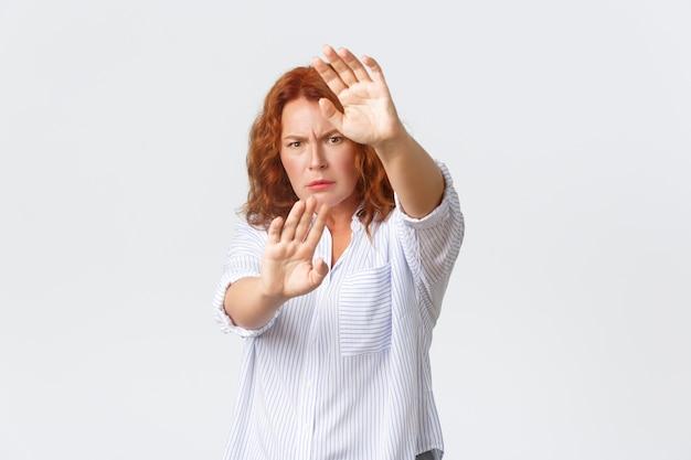 深刻に見える心配そうで不機嫌な赤毛の中年女性が身を守る