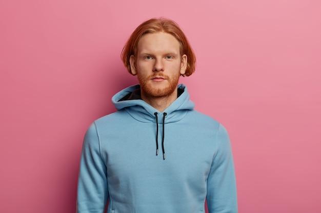 Uomo barbuto fiducioso dall'aspetto serio con capelli rossi