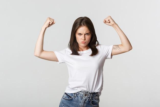 Серьезно выглядящая уверенная в себе брюнетка девушка сгибает бицепсы, показывая сильные стороны.