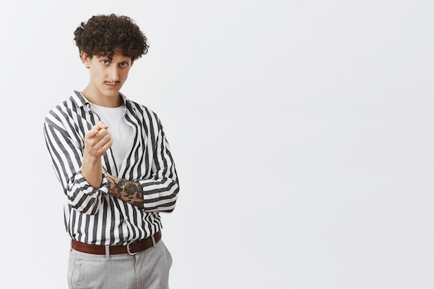 Serious-looking daring and bossy good-looking stylish male designer with dark curly hair moustache and tattoos on arms pointing with blameful look frowning looking strict from under forehead