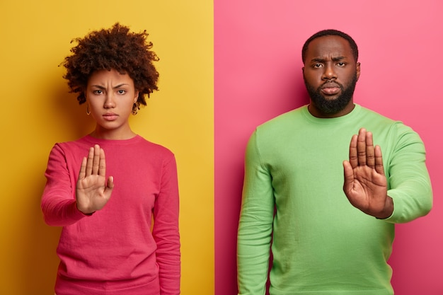Serious looking dark skinned woman and man extend palms