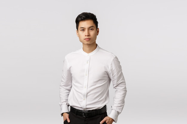Serious-looking, determined successful wealthy asian businessman in white collar shirt, black pants, hold hands in pockets, looking camera, listening employee report about business,