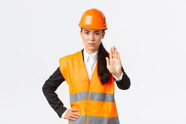 真面目そうに見える失望したアジアの女性建築家、安全ヘルメットをかぶった作業エリアの建設マネージャー、停止ジェスチャーを示し、行動を禁止し、不法侵入を禁止し、白い背景