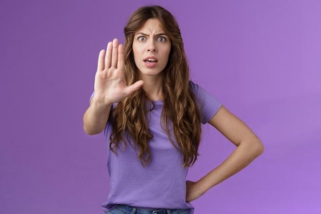 真面目そうな不機嫌な断定的な女性の友人は、自信を持って喫煙をやめ、手のひらカメラを引っ張って、不承認のジェスチャーを禁止し、あなたが悪い選択をすることを抑制します紫色の背景。