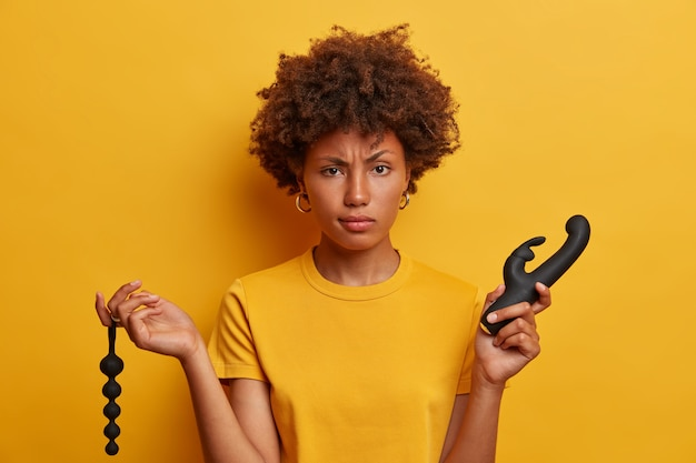 아프로 머리카락을 가진 진지한 불쾌한 여성은 섹스 샵에서 항문 구슬과 진동기 중에서 선택하고 클리토리스와 g 스팟, 즐거운 침투를위한 도구가 필요합니다. 오르가즘과 즐거움
