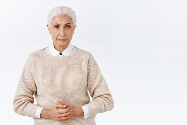 Serious-looking elegant senior teacher, principal on duty, wear office outfit, sweater over blouse, hold hands together over chest, stare camera strict and determined, assertive white wall