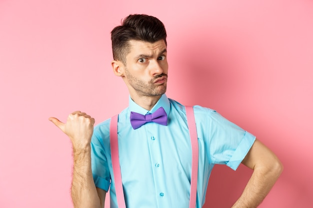 Serious-looking guy in suspenders suggessting to go outside, pointing left and looking confident at camera, starting fight, standing over pink background.
