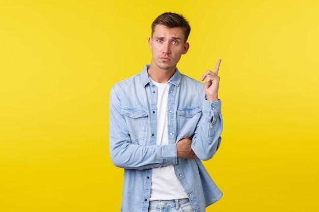 Серьезно выглядящий красивый мужчина-гей в джинсовой рубашке, подняв указательный палец, высказал предположение, сказал, что его идея или план, нашел хорошее решение, стоя на желтом фоне определенно.