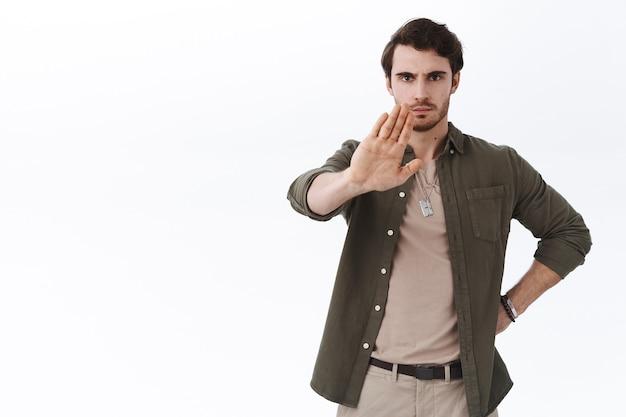 Серьезно выглядящий мужчина-руководитель команды поднимает руку, чтобы сказать «стоп», хмурясь, предупреждает, не согласен с человеком, выражает резкое неодобрение