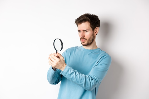 Serious-looking man looking through magnifying glass, investigating something, found interesting promo, standing on white background