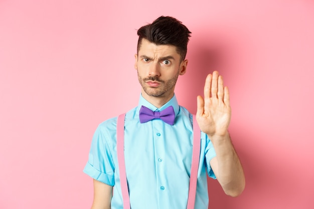 Serious-looking man prohibit something bad, stretch out hand to stop you, forbid action, saying no and looking strict, standing over pink.