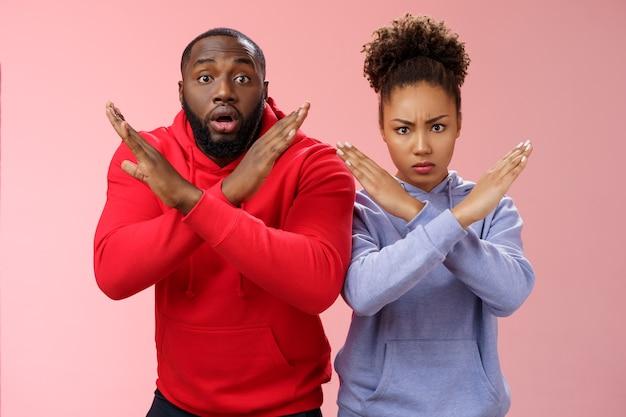 Serio dall'aspetto nervoso in preda al panico due ragazzo afroamericano ragazza che mostra il gesto di arresto incrociato l'uomo si sente preoccupato scioccato chiedendo di non fare azione proibita donna arrabbiata guarda la domanda della telecamera esci