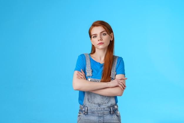 진지해 보이는 전문적인 빨간 머리 여성 솜씨 있는 소녀, 팔짱을 끼고 자신감 넘치는 포즈를 취하고 카메라를 보고 감정을 엄격하게 결정하지 않고 목표를 달성하고 파란색 배경을 권장합니다.