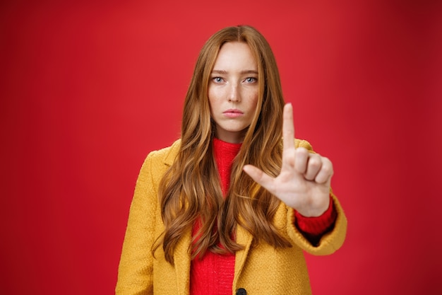 黄色いコートを着た真面目な赤毛の女性がカメラに手を伸ばし、停止と警告のジェスチャーを禁止および禁止することで、赤い壁に自信を持っているような感情のない顔をしています。