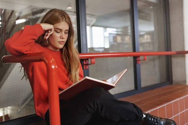 Серьезная рыжая женщина сидит на скамейке в помещении, читая книгу с упором.