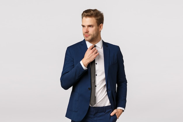 Serious-looking sassy businessman in blue classis suit, adjusting tie and looking away, holding hand in pocket, getting ready for work, waiting cab in downtown to go business meeting, greet partners