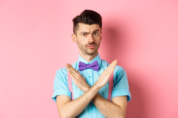 Serious-looking skeptical guy showing cross sign to stop, prohibit something bad, forbid action, standing on pink background. copy space