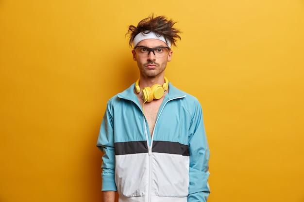 Sportivo dall'aspetto serio posa con le cuffie, vestito con abbigliamento sportivo, pronto per l'esercizio indoor, guarda con sicurezza, pratica aerobica per uno stile di vita sano, posa sul muro giallo