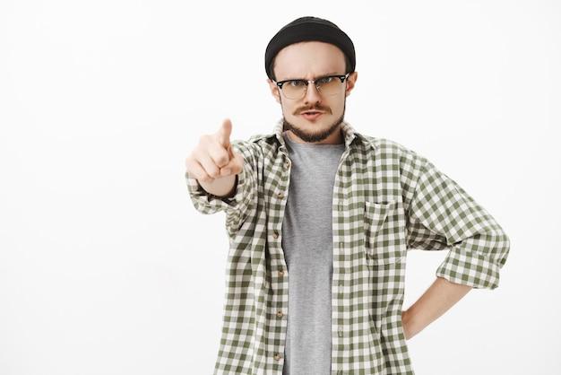 Insegnante di musica maschio giovane severo e irritato dall'aspetto serio in berretto nero e occhiali con baffi in piedi in posa furiosa che punta in avanti