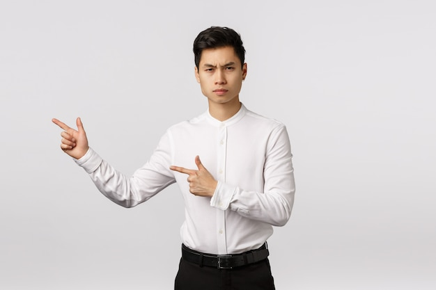 Serious-looking strict and unsatisfied young asian man disappointed with painting hanging wrong. businessman looking camera sulking and frowning displeased, pointing left to turn attention at mistake