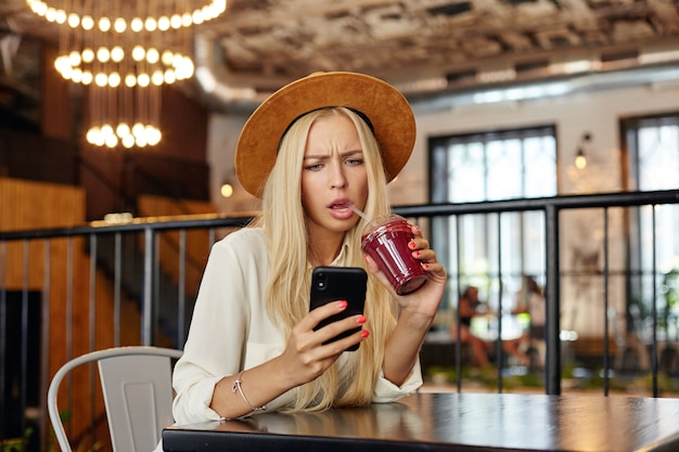 Serious looking surprised young long haired blonde woman reading unexpected news with displeased face, drinking berry drink with straw while sitting at table over modern cafe