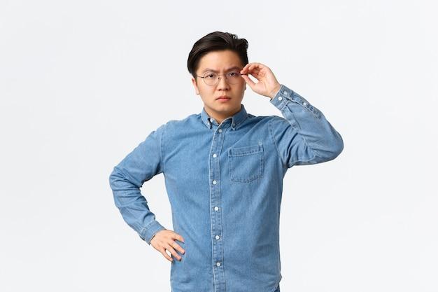 真面目な顔つきの疑わしいアジア人男性起業家が顔に眼鏡をかけ、疑わしく眉をひそめ、躊躇したり懐疑的に立ったり、誰かを信用してはいけない、不確かな白い背景を提起する