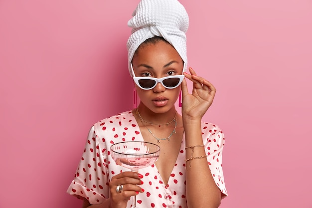 Serious looking tender woman with dark skin, looks confidently, wears sunglasses, holds glass of cocktail, dressed casually, wrapped towel on washed hair, enjoys peaceful atmosphere