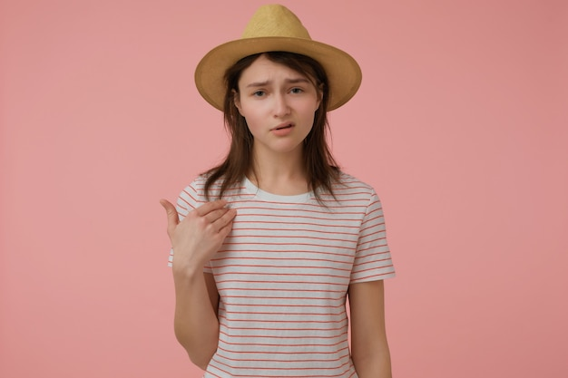 Serious looking woman, confident girl with long brunette hair. wearing t-shirt with red strips and hat. pointing at herself.  isolated over pastel pink wall