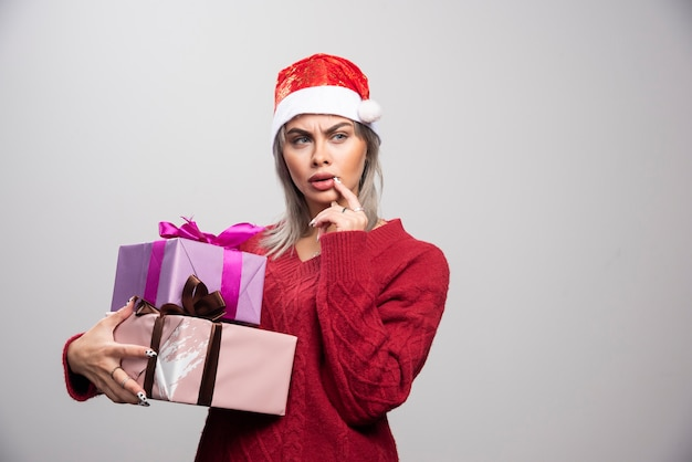 Serious looking woman in santa hat holding christmas gifts.