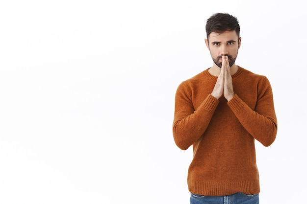 Serious-looking worried and concerned handsome bearded man, praying for world cure from covid19, hold hands near lips  awaiting news or important results, white wall