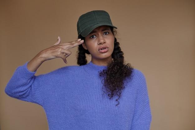 Giovane donna dalla pelle scura dall'aspetto serio che mantiene i suoi capelli castani ricci in trecce e pistola pieghevole con la mano alzata, sopracciglia accigliate mentre è in piedi