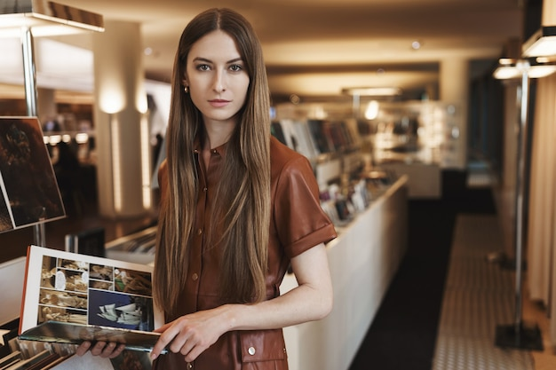 Serious-looking young female picking design magazines at vintage store, standing in stylish brown dress.