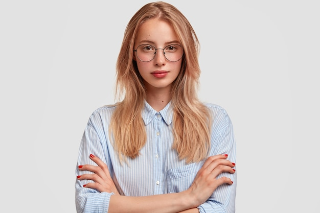 Serious lovely woman student in spectacles, keeps hands folded, listenes attentively professor`s lecture, wears elegant shirt