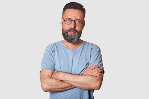 Serious magnetic black haired man posing with folded arms, having strong look, determined facial expression, having athletic arms. middle aged bearded model poses isolated on light grey.
