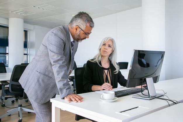 Серьезные коллеги мужского и женского пола, сидя и стоя на рабочем месте с пк, обсуждая бумажный отчет. концепция делового общения