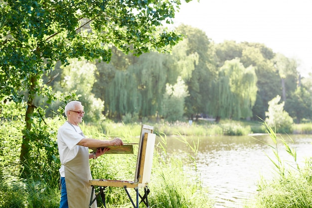 Serious male artist holding brush and painting picture on easel on open air.