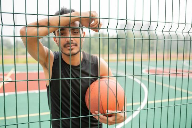 Серьезный баскетболист мужского пола с мячом, стоящим напротив сетки, глядя на вас во время перерыва на детской площадке