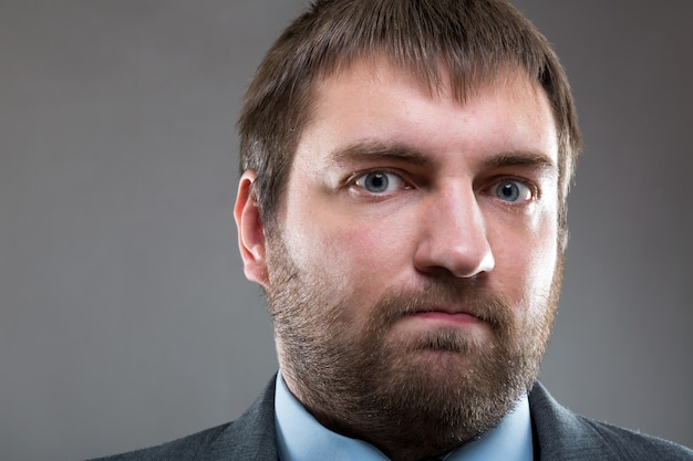 Serious male bearded face close up portrait