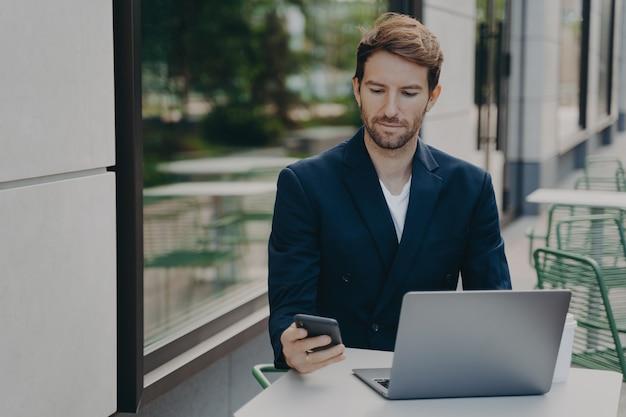 Серьезный мужчина-босс, одетый в элегантную одежду, работает онлайн на портативном компьютере с сотовой связью