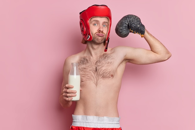 Serious male boxer raises arm and shows muscles demonstrates his power looks directly at camera drinks milk