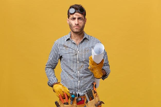 체크 무늬 셔츠, 보호 안경 및 노란색 벽 위에 절연 서류를 손에 들고 장갑을 착용하는 악기의 벨트와 심각한 남성 작성기. 사람, 수리 및 건설