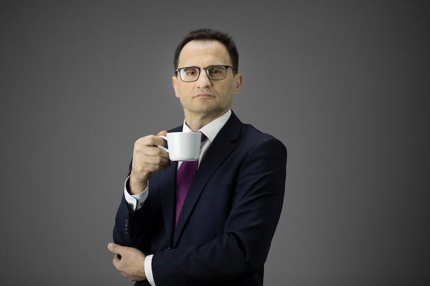 カメラ目線の朝のコーヒーカップとグラスで深刻な男性ビジネスマン