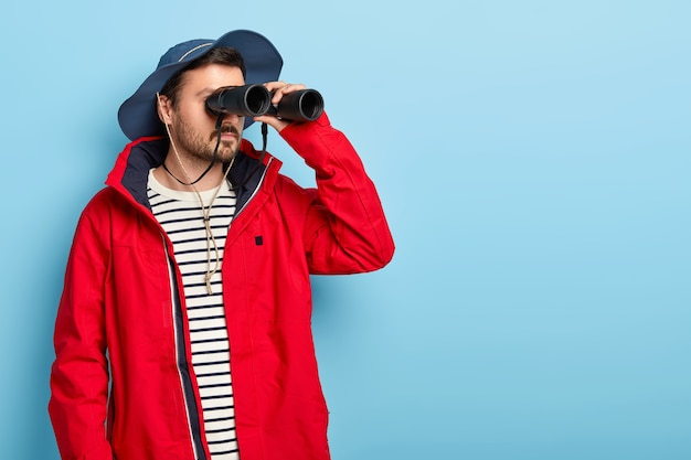 Serious male camper has long adventurous journey, keeps binoculars near eyes, wears hat and red jacket, tries to see something far away, poses against blue wall