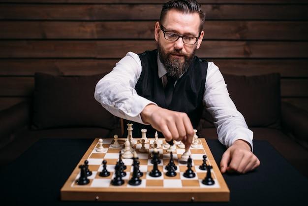 Серьезный шахматист мужского пола в очках делает ход победы.