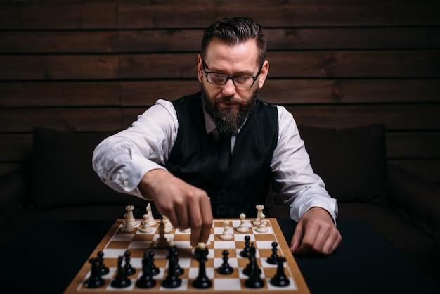 深刻な男性のチェスプレーヤーが勝利をもたらす