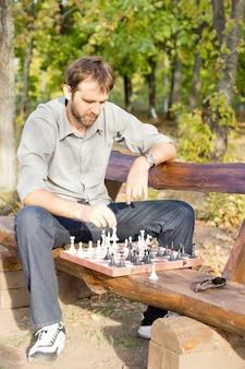 Серьезный шахматист мужского пола, сидящий на деревянной скамейке с шахматной доской перед ним, делает ход