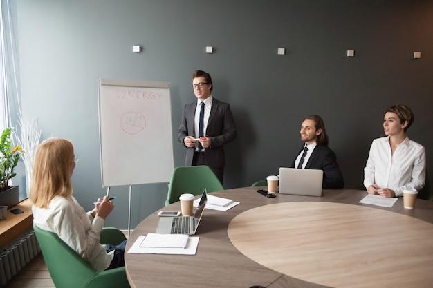 Серьезный мужской тренер дает представление на флипчарте коллегам по бизнесу