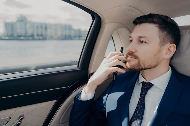 파란색 정장을 입은 진지한 남성 회사 임원은 중요한 심각한 결정을 내리고 위험과 이익을 중시하고 리무진에 앉아 있는 동안 턱에 전화기를 들고 있습니다.